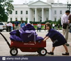 Ava Cohen Crawford pushes a wagon filled with petitions protesting U.S  President George W. Bush's veto of the State Children's Health Insurance  Program in front of the White House in Washington, October
