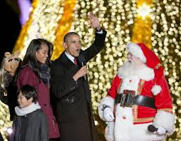 President Obama, center, waves to the crowd as he walks off the stage with  his daughter Malia, left, during the National Christmas Tree Lighting  ceremony at ...