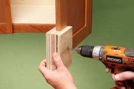 cabinet handle jig. man assemblling a two-sided jig to slot onto the edge of cabinet door handle