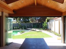 frameless sliding glass doors that open up to a private back yard terrace and pool