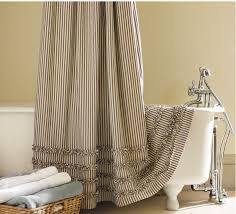 shower curtain with tiny vertical strips patterns a large white bathtub with flawfeet a rattan basket for towel supplies