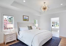 absolutely beautiful bedroom features a nickel sputnik pendant arteriors zanadoo chandelier hanging over a white tufted wingback bed adorned with a