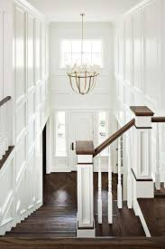 chic two story foyer features walls clad in decorative trim moldings illuminated by a brass chandelier lancaster chandelier