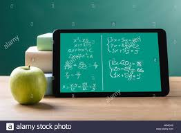 close up of green apple and digital tablet with mathematical equations on screen stock