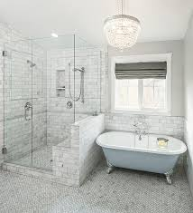 view in gallery bathroom in soft grey and blue with herringbone floors and a painted bathtub