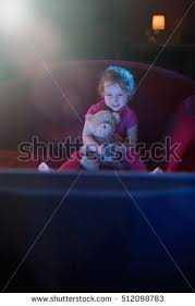 kids watching tv at night. at home by night. a lonely little girl sitting on red couch watching tv kids night p