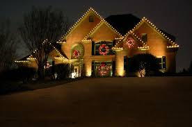 outdoor lighting perspective. Large Lit Wreaths With Bright Red Bows Hang At Different Places On The Front Facade And String Lights Line Roof For A Festive Outdoor Lighting Perspective I