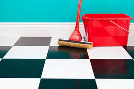 a mop and bucket sits on a black and white linoleum tiled floor