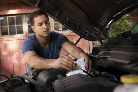 man fixing car regular maintenance