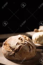 Freshly Baked Bread On Wooden Table On Dark Background Stock Photo