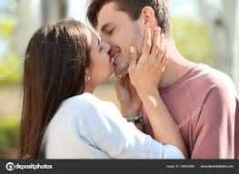young lovely couple kissing outdoors stock photo
