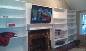 large white wooden cabinet with tv on the top and brown wooden fireplace under it