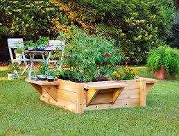 small raised backyard vegetable garden with unique wooden container bed also white crisscross framed chairs and table