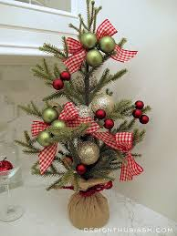 tabletop christmas trees. this is an elegant tabletop christmas tree decorated with red bows and striking green baubles. trees h