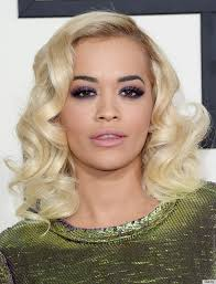 rita ora matches her blonde hair and green dress with a dramatic purple smokey eye makeup
