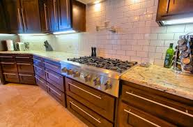 a contemporary kitchen with high end appliances and a beautiful white subway tile backsplash brown cabinets w26 brown
