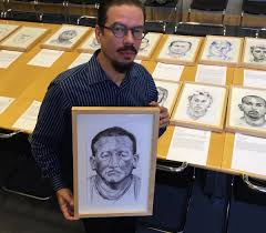 jose alvarez holding his portrait of roberto from guatemala preparing for his exhibit at the boca raton museum of art