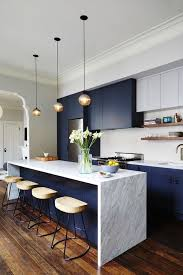 a waterfall countertop gives this modern navy kitchen a sleek and clean look