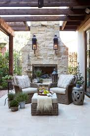 A Seating Area Is Set Around An Outdoor Limestone Fireplace At This French Country  Home