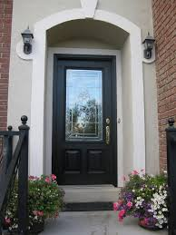 exterior glass and black wooden entry doors connected by double black wall light on beige