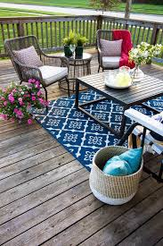 a colorful eclectic deck with a bright rug wicker and wooden furniture colorful textiles