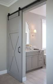 Gray walls highlight a gray barn door on black rails leading to an en suit  bathroom featuring a gray washstand accented with polished nickel hardware  and ...