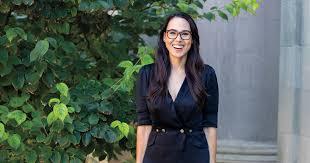 Under her coat, ella wore a burgundy dress by batsheva — a jewish designer — with a ruffled trim and ruffled sleeves. Meena Harris 12 Harvard Law Today