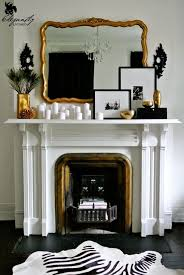 gold mirror fireplace mantel white candles framed photographs black white and