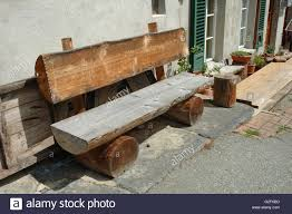 furniture made from tree trunks. old wooden bench made of tree trunk standing at building wall furniture from trunks