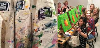 painting smocks covered in paint and a group of young women painting canvases while drinking wine