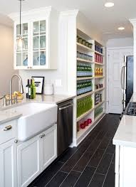 galley kitchen with white cabinets paired with white granite countertop as well as farmhouse sink accented with satin nickel gooseneck faucet over porcelain