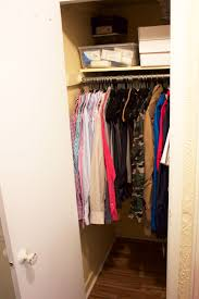 an organized decluttered closet with shirts jackets and pants hanging and storage containers