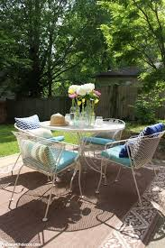 a tan metal patio set with aqua cushions pillows and glass vases flowers centerpiece