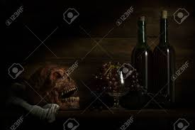 still life photography human skulls book wine and grap on black table against