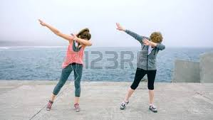 dabb dance. senior and young woman making dab dance outdoors by sea pier dabb