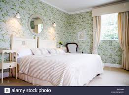 Wall-lights above bed with cream bed-cover in traditional country bedroom  with green wallpaper and window with cream curtains
