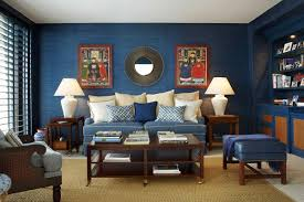 classic blue living room design with blue wall blue sofa plus table pillows and beige rugs