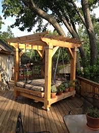 natural backyard with wooden deck and cozy swinging bed combine with wooden railing and potted plant