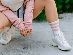 a woman squatting down wearing white sneakers