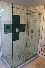 The clear glass enclosure and door reveal the custom tile design and  accents in this shower