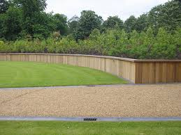simple oak retaining wall ideas and green grass areas beside brown pebble way near green trees