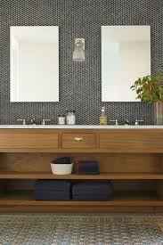 natural bathroom with black and grey penny tiles in the sink area