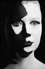 white face painted fashion model s face in white paint before applying layers of black paint