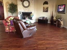 dark brown color best vinyl wood plank flooring for living room with brown leather rocking chair sofa with flower pattern fabric cover stone wall fireplace