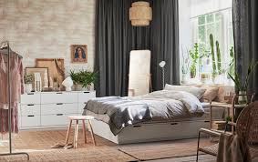 White bed with drawers in a large bedroom with exposed brick, gray curtains  and jute