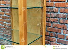 wooden shelving with empty glass shelves brick wall