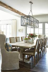table seating two gray linen wingback captain s chairs and eight light gray french square back dining chairs lit by a gray iron rectangular chandelier