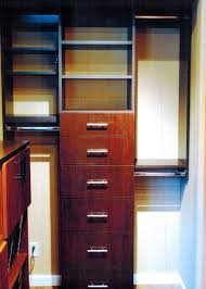 it has storage cubes shelving and hanging mechanism the next part is another storage cabinet made with a walnut wood it has pullout baskets with behind