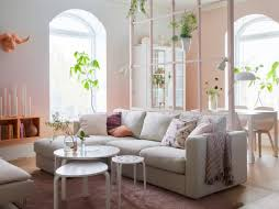A pink and white living room with beige sofa with chaise longues and the  hint of
