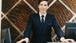 portrait of a male hotel receptionist standing behind a reception desk